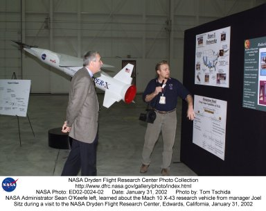 NASA Administrator Sean O'Keefe left, learned about the Mach 10 X-43 research vehicle from manager, Joel Sitz during O'Keefe's visit to the NASA Dryden Flight Research Center, Edwards, California, January 31, 2002.
