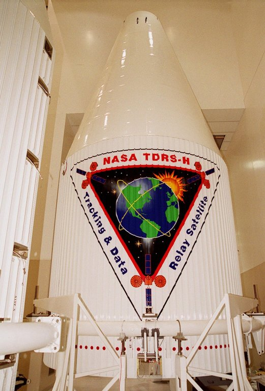 The logo for the Tracking and Data Relay Satellite (TDRS-H) is predominantly displayed on the fairing that will encapsulate the satellite for launch. The fairing is in KSC?s Spacecraft Assembly and Encapsulation Facility (SAEF-2) where TDRS is undergoing testing. The TDRS is scheduled to be launched from CCAFS June 29 aboard an Atlas IIA/Centaur rocket. One of three satellites (labeled H, I and J) being built in the Hughes Space and Communications Company Integrated Satellite Factory in El Segundo, Calif., the latest TDRS uses an innovative springback antenna design. A pair of 15-foot-diameter, flexible mesh antenna reflectors fold up for launch, then spring back into their original cupped circular shape on orbit. The new satellites will augment the TDRS system?s existing Sand Ku-band frequencies by adding Ka-band capability. TDRS will serve as the sole means of continuous, high-data-rate communication with the space shuttle, with the International Space Station upon its completion, and with dozens of unmanned scientific satellites in low earth orbit