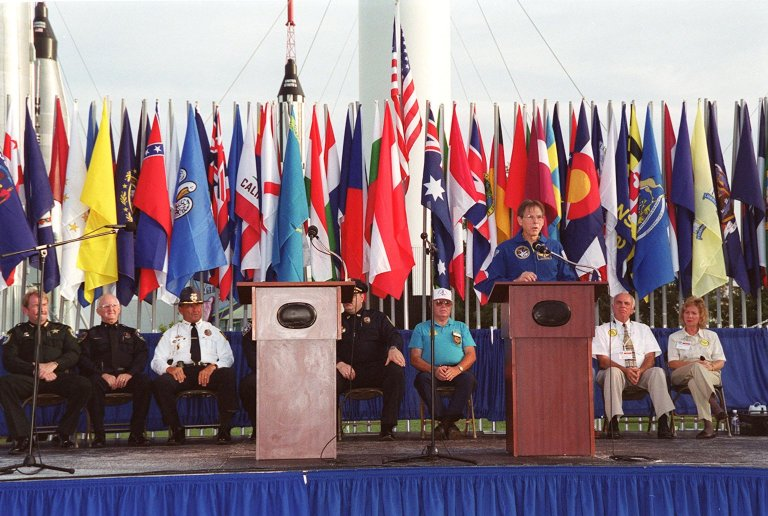 During opening ceremonies of the 2000 International Law Enforcement Games, astronaut Sam Durrance addresses an audience of 1,850 participants and their families. Held in the KSC Visitor Complex Rocket Garden, the ceremony included parades, torch lighting and a tug of war. The games feature officers from 15 countries and 37 United States in competitions around Brevard County, Fla