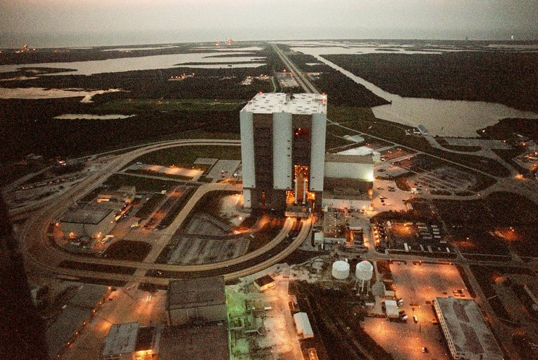 """KENNEDY SPACE CENTER, FLA. -- At 6:30 a.m. EDT an aerial view captures a first in Space Shuttle history: a fully stacked Shuttle - Atlantis - is rolling into the Vehicle Assembly Building's (VAB) high bay 2 on the building's west side (center of photo). The VAB and nearby rock-paved crawlerway (circling to the left) have recently undergone major modifications to provide Shuttle fliglht hardware more storage space and protection - """"Safe Haven"""" - from hurricanes or tropical storms. Atlantis, the twin solid rocket boosters and external tank begain moving out of VAB high bay 1 on the east side at 2:59 a.m. EDT. The 6-million pound crawler transporter carried the Mobile Launcher Platform and Space Shuttle around the north side of the VAB and into high bay 2. To the right of the VAB is the turn basin. In the background can be seen both Launch Pads with the Atlantic Ocean behind them. After the successful """"Safe Haven"""" fit check, Shuttle Atlantis is scheduled to roll out to Launch Pad 39B in preparation for the STS-106 launch on Sept. 8."""
