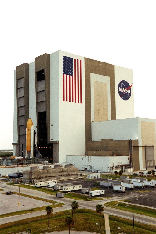"""KENNEDY SPACE CENTER, FLA. -- For the first time in Space Shuttle history, a fully stacked Shuttle - Atlantis - is rolling into the Vehicle Assembly Building's (VAB) high bay 2 on the building's west side. The VAB and nearby rock-paved crawlerway have recently undergone major modifications to provide Shuttle fliglht hardware more storage space and protection - """"Safe Haven"""" - from hurricanes or tropical storms. Atlantis, the twin solid rocket boosters and external tank begain moving out of VAB high bay 1 on the east side at 2:59 a.m. EDT. The 6-million pound crawler transporter carried the Mobile Launcher Platform and Space Shuttle around the north side of the VAB and into high bay 2. After the successful """"Safe Haven"""" fit check, Shuttle Atlantis is scheduled to roll out to Launch Pad 39B in preparation for the STS-106 launch on Sept. 8."""