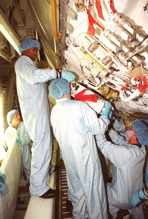 Workers perform a fit check on a Power Data Grapple Fixture (PDGF) in the Space Station Processing Facility. The PDGF is part of the payload on mission STS-98, a flight to the International Space Station. During the mission, the crew will install the U.S. Lab in the Space Station during a series of three space walks. The STS-98 mission will provide the station with science research facilities and expand its power, life support and control capabilities