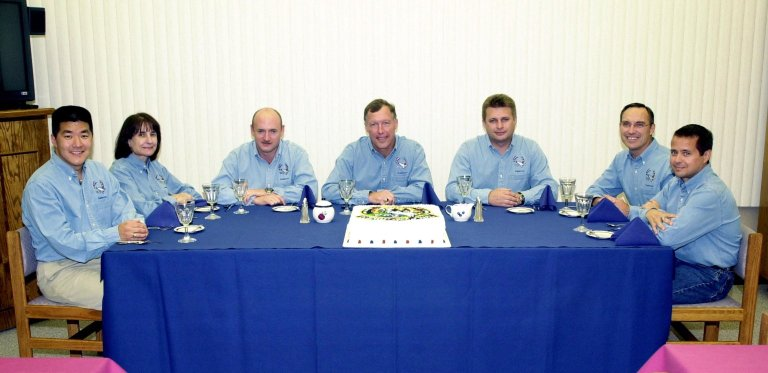 KENNEDY SPACE CENTER, Fla. - The STS-108 and Expedition 4 crews enjoy a traditional pre-launch meal, complete with a cake decorated with the Mission Patch. Seated from left to right are STS-108 Mission Specialists Daniel M. Tani and Linda A. Godwin, Pilot Mark E. Kelly and Commander Dominic L. Gorie; the Expedition 4 crew Commander Yuri Onufrienko and astronauts Carl E. Walz and Daniel W. Bursch. Top priorities for the STS-108 (UF-1) mission of Endeavour are rotation of the International Space Station Expedition 3 and Expedition 4 crews; bringing water, equipment and supplies to the station in the Multi-Purpose Logistics Module Raffaello; and the crew's completion of robotics tasks and a spacewalk to install thermal blankets over two pieces of equipment at the bases of the Space Station's solar wings. Launch is scheduled for 5:45 p.m. EST Dec. 4, 2001, from Launch Pad 39B