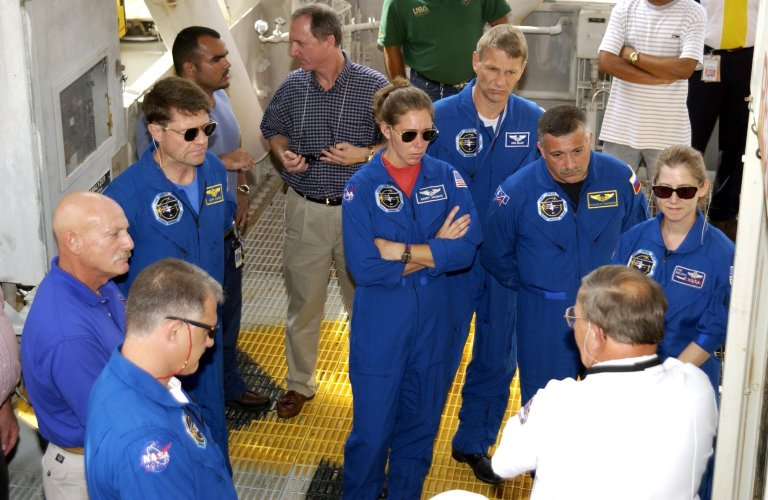 KENNEDY SPACE CENTER, FLA. -- During emergency egress training from the launch pad, the STS-112 crew listens to a trainer about use of the system. The crew members are, from left in the center, Commander Jeffrey Ashby, Mission Specialists Sandra Magnus, Piers Sellers and Fyodor Yurchikhin; and Pilot Pamela Melroy. In the foreground, left, is Mission Specialist David Wolf. Yurchikhin is with the Russian Space Agency. The training is part of Terminal Countdown Demonstration Test activities, which include a simulated launch countdown. Mission STS-112 aboard Space Shuttle Atlantis is scheduled to launch no earlier than Oct. 2, between 2 and 6 p.m. EDT. STS-112 is the 15th assembly mission to the International Space Station. Atlantis will be carrying the S1 Integrated Truss Structure, the first starboard truss segment, to be attached to the central truss segment, S0, and the Crew and Equipment Translation Aid (CETA) Cart A. The CETA is the first of two human-powered carts that will ride along the ISS railway, providing mobile work platforms for future spacewalking astronauts.
