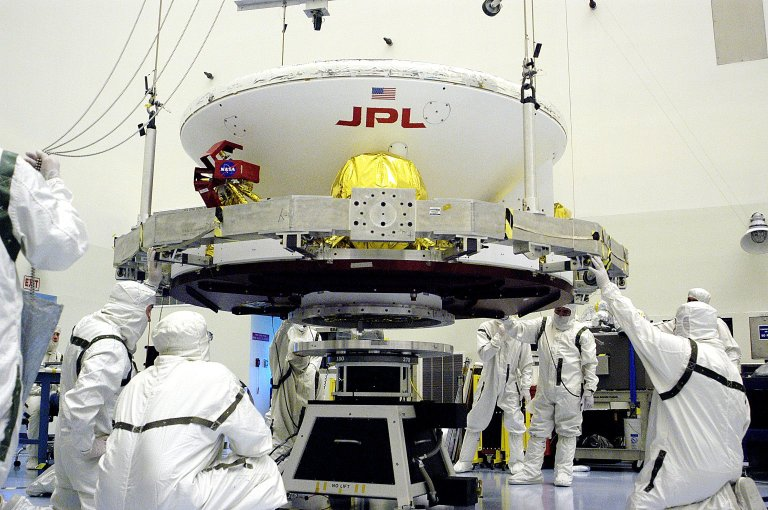 KENNEDY SPACE CENTER, FLA. - In the Payload Hazardous Servicing Facility, workers prepare to lift the Mars Exploration Rover-1 (MER-B) onto a spin table during preflight processing of the spacecraft. The rover is scheduled to launch aboard a Delta II rocket on June 25. NASA?s twin Mars Exploration Rovers are designed to study the history of water on Mars. These robotic geologists are equipped with a robotic arm, a drilling tool, three spectrometers, and four pairs of cameras that allow them to have a human-like, 3D view of the terrain. Each rover could travel as far as 100 meters in one day to act as Mars scientists' eyes and hands, exploring an environment where humans are not yet able to go. The launch of MER-2 (MER-A) is tentatively set for June 8.