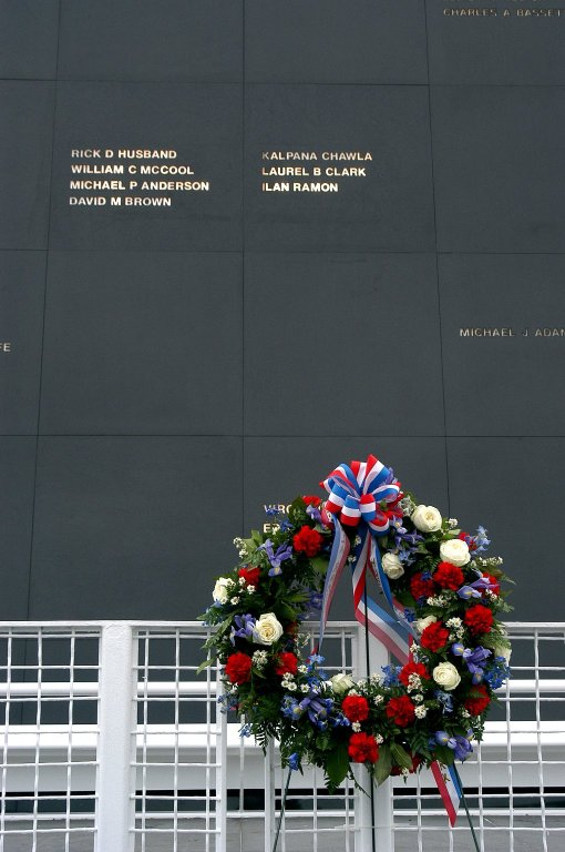 """KENNEDY SPACE CENTER, FLA. - A ceremonial wreath is placed at the Space Mirror Memorial at the Kennedy Space Center Visitor Complex. During this dedication ceremony, the names of the STS-107 astronauts who lost their lives during the Columbia accident -- Rick Husband, Willie McCool, Laurel Clark, Michael Anderson, David Brown, Kalpana Chawla, and Ilan Ramon -- join the names of 17 other space heroes who gave their lives for the U.S. space program. The """"Space Mirror,"""" 42 1/2 feet high by 50 feet wide, illuminates the names of the fallen astronauts cut through the monument's black granite surface."""