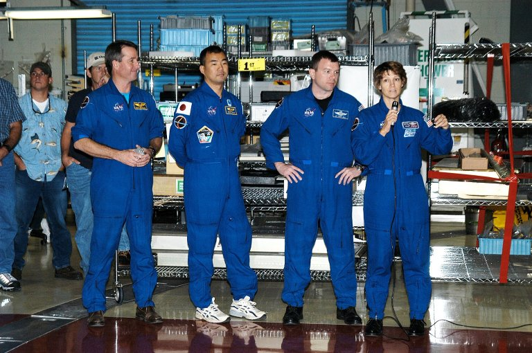 KENNEDY SPACE CENTER, FLA. - (From left) STS-114 Mission Specialists Stephen Robinson and Soichi Noguchi, Pilot James Kelly and Commander Eileen Collins talk to workers in the Orbiter Processing Facility. Noguchi is with the Japan Aerospace Exploration Agency, JAXA. The STS-114 crew is at KSC to take part in crew equipment and orbiter familiarization.