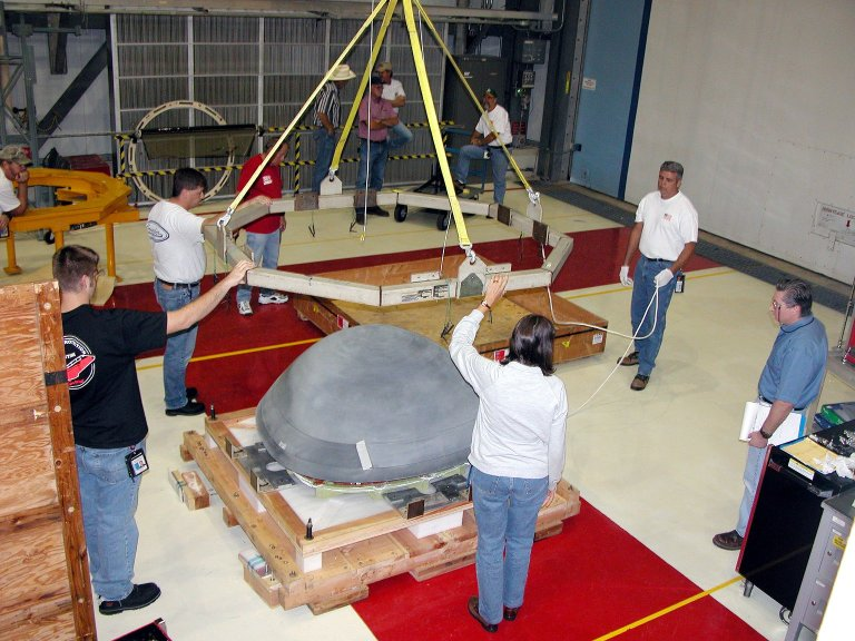 KENNEDY SPACE CENTER, FLA. - In the Orbiter Processing Facility, workers remove the overhead crane from the nose cap that was removed from Atlantis. The reinforced carbon-carbon (RCC) nose cap is being sent to the original manufacturing company, Vought in Ft. Worth, Texas, a subsidiary of Lockheed Martin, to undergo non-destructive testing such as CAT scan and thermography.