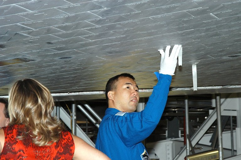 KENNEDY SPACE CENTER, FLA. - In the Orbiter Processing Facility, STS-114 Mission Specialist Soichi Noguchi takes a close look at the some of the tiles underneath Atlantis. Noguchi is with the Japan Aerospace Exploration Agency, JAXA. The STS-114 crew is at KSC to take part in crew equipment and orbiter familiarization.