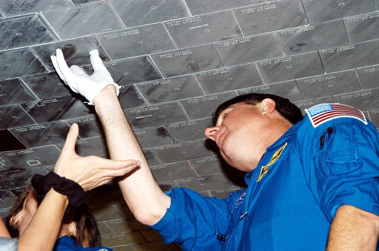 KENNEDY SPACE CENTER, FLA. - In the Orbiter Processing Facility, STS-114 Mission Specialist Stephen Robinson takes a close look at the some of the tiles underneath Atlantis. The STS-114 crew is at KSC to take part in crew equipment and orbiter familiarization.