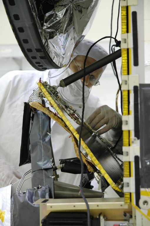 KENNEDY SPACE CENTER, FLA. -- In the Astrotech Space Operations facility, Orbital Science technicians install a computer chip on the Dawn spacecraft. The silicon chip holds the names of more than 360,000 space enthusiasts worldwide who signed up to participate in a virtual voyage to the asteroid belt and is about the size of an American five-cent coin. Dawn's mission is to explore two of the asteroid belt's most intriguing and dissimilar occupants: asteroid Vesta and the dwarf planet Ceres. Dawn is scheduled to launch June 30 from Launch Complex 17-B. Photo credit: NASA/Jim Grossmann