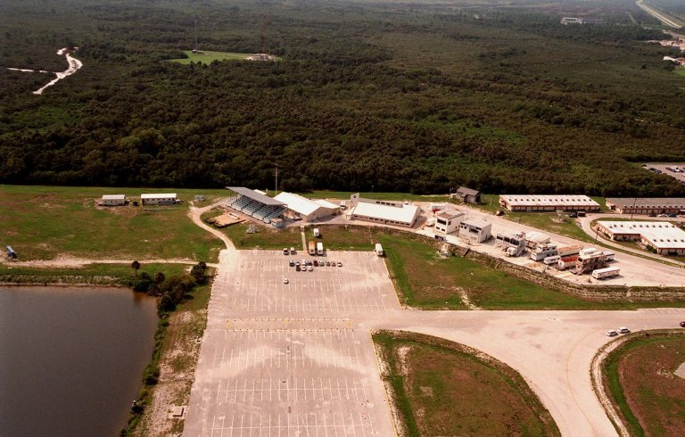 On a normal day of activity prior to the launch of mission STS-95, the parking lot (foreground), plus the grandstand and buildings at the Press Site (beyond and to the right), are easily located from the air. The view gives no indication of the media frenzy the launch would generate with the return to space of John H. Glenn Jr., a senator from Ohio, whose first flight was aboard Friendship 7 in February 1962, and the first American to orbit the Earth. Glenn is one of a crew of seven on board Space Shuttle Discovery for the nine-day mission
