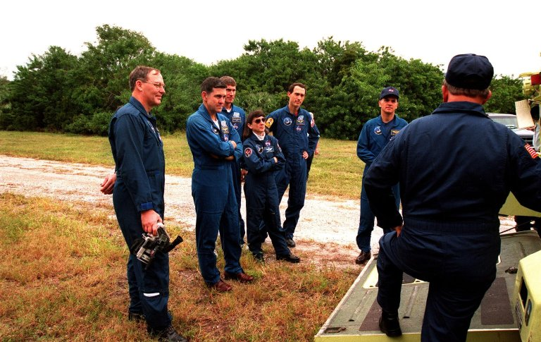 """The STS-88 crew receives instruction on the operation of an M-113, an armored personnel carrier, as part of emergency egress training from George Hoggard (back to camera) during Terminal Countdown Demonstration Test (TCDT) activities. From left to right, they are Mission Specialist Jerry L. Ross; Mission Commander Robert D. Cabana; Mission Specialist Sergei Konstantinovich Krikalev, a Russian cosmonaut; Mission Specialist Nancy J. Currie; Mission Specialist James H. Newman; and Pilot Frederick W. """"Rick"""" Sturckow. The TCDT also provides the crew with simulated countdown exercises and opportunities to inspect their mission payloads in the orbiter's payload bay. Mission STS-88 is targeted for launch on Dec. 3, 1998. It is the first U.S. flight for the assembly of the International Space Station and will carry the Unity connecting module"""