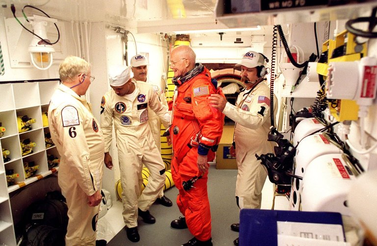 In the environmental chamber known as the white room, STS-95 Payload Specialist John H. Glenn Jr., senator from Ohio, is prepared by closeout room crew members Danny Wyatt (left to right), Carlous Gillis, Jim Kelly and Travis Thompson for entry into the Space Shuttle Discovery for his second flight into space after 36 years. The STS-95 mission, targeted for launch at 2 p.m. EST on Oct. 29, is expected to last 8 days, 21 hours and 49 minutes, and return to KSC at 11:49 a.m. EST on Nov. 7