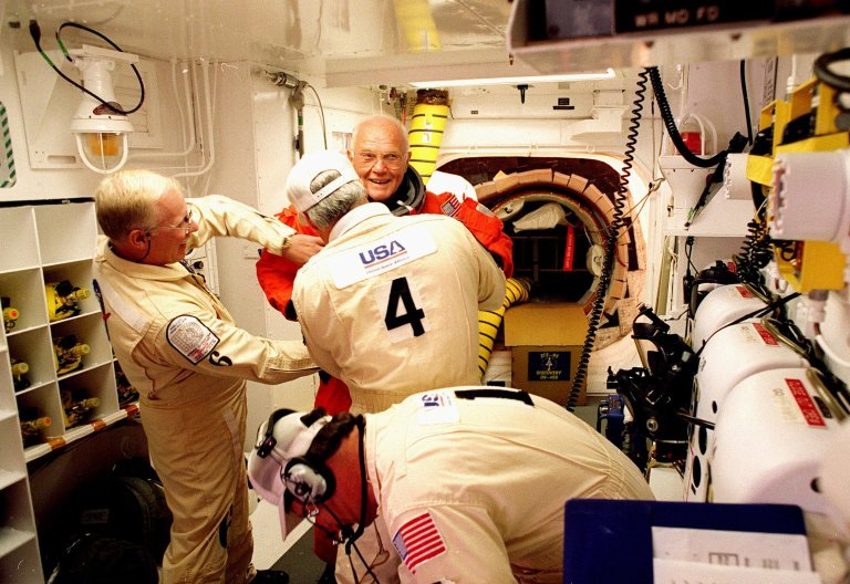 In the environmental chamber known as the white room, an eager STS-95 Payload Specialist John H. Glenn Jr., senator from Ohio, has his flight suit checked by closeout room crew members Danny Wyatt (left to right), Chris Meinert and Travis Thompson (foreground) for entry into the Space Shuttle Discovery for his second flight into space after 36 years. The STS-95 mission, targeted for launch at 2 p.m. EST on Oct. 29, is expected to last 8 days, 21 hours and 49 minutes, and return to KSC at 11:49 a.m. EST on Nov. 7