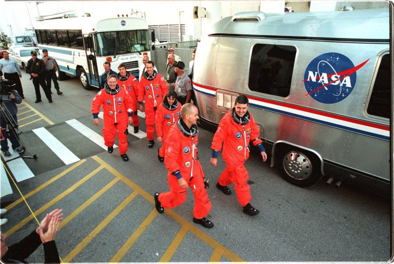 """After suiting up for their practice countdown exercise, STS-88 crew members head for the bus outside the Operations and Checkout Building for the trip to Launch Pad 39A. From left they are Mission Specialist Jerry L. Ross, Mission Specialist Sergei Krikalev, who is a Russian cosmonaut, Mission Specialists James H. Newman and Nancy J. Currie, Pilot Frederick W. """"Rick"""" Sturckow, and Mission Commander Robert D. Cabana. The crew are at KSC to participate in the Terminal Countdown Demonstration Test (TCDT) which includes mission familiarization activities, emergency egress training, and the simulated main engine cut-off exercise. Mission STS-88 is targeted for launch on Dec. 3, 1998. It is the first U.S. flight for the assembly of the International Space Station and will carry the Unity connecting module"""