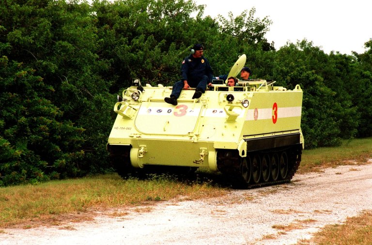 """STS-88 Mission Specialist Sergei Konstantinovich Krikalev, a Russian cosmonaut, operates an M-113, an armored personnel carrier, as part of emergency egress training under the watchful eye of instructor George Hoggard (left) during Terminal Countdown Demonstration Test (TCDT) activities. The TCDT also provides the crew with simulated countdown exercises and opportunities to inspect their mission payloads in the orbiter's payload bay. Mission STS-88 is targeted for launch on Dec. 3, 1998. It is the first U.S. flight for the assembly of the International Space Station and will carry the Unity connecting module. Others in the STS-88 crew are Mission Commander Robert D. Cabana; Pilot Frederick W. """"Rick"""" Sturckow; and Mission Specialists Nancy J. Currie, Jerry L. Ross, and James H. Newman"""