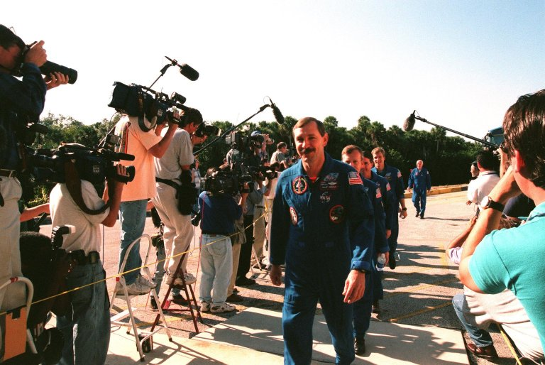 Members of the STS-95 crew file past photographers and reporters from all over the world as they enter the Kennedy Space Center Press Site Auditorium to participate in a media briefing before returning to the Johnson Space Center in Houston, Texas. From left to right, they are Mission Commander Curtis L. Brown Jr.; Pilot Steven W. Lindsey; Mission Specialist and Payload Commander Stephen K. Robinson; Mission Specialist Scott E. Parazynski; and Payload Specialist John H. Glenn Jr., a senator from Ohio and one of the original seven Project Mercury astronauts. The other STS-95 crew members participating in the briefing (but hidden behind Parazynski) are Mission Specialist Pedro Duque, with the European Space Agency (ESA), and Payload Specialist Chiaki Mukai, with the National Space Development Agency of Japan (NASDA). The STS-95 mission ended with landing at Kennedy Space Center's Shuttle Landing Facility at 12:04 p.m. EST on Nov. 7. The mission included research payloads such as the Spartan-201 solar-observing deployable spacecraft, the Hubble Space Telescope Orbital Systems Test Platform, the International Extreme Ultraviolet Hitchhiker, as well as a SPACEHAB single module with experiments on space flight and the aging process