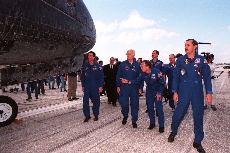 After leaving the Crew Transport Vehicle, members of the mission STS-95 crew (foreground) take a close look at the orbiter Discovery that carried them for nine days and 3.6 million miles. From left, they are Mission Specialist Stephen K. Robinson; Payload Specialist John H. Glenn Jr., a senator from Ohio; Pilot Steven W. Lindsey; and Mission Commander Curtis L. Brown Jr. The STS-95 crew completed a successful mission, landing at the Shuttle Landing Facility at 12:04 p.m. EST, after 9 days in space, traveling 3.6 million miles. The mission included research payloads such as the Spartan solar-observing deployable spacecraft, the Hubble Space Telescope Orbital Systems Test Platform, the International Extreme Ultraviolet Hitchhiker, as well as the SPACEHAB single module with experiments on space flight and the aging process