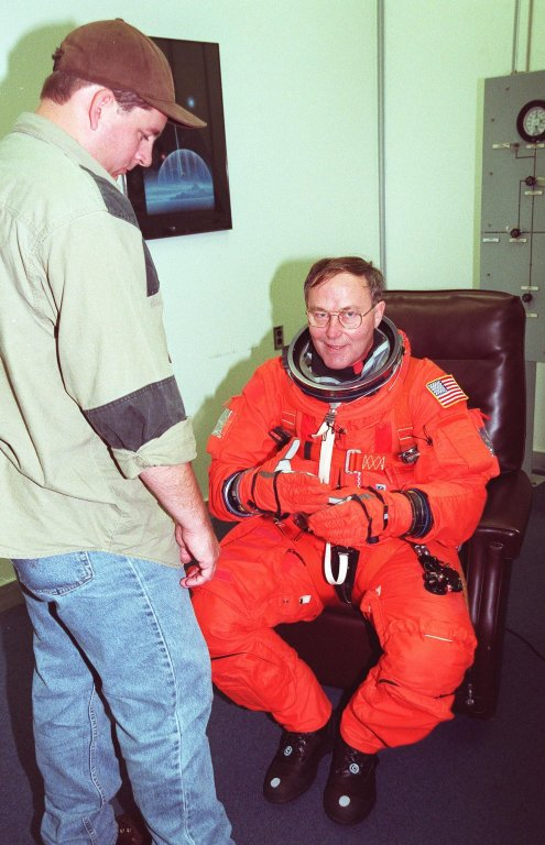 STS-88 Mission Specialist Jerry L. Ross (right) suits up in the Operations and Checkout Building, as part of a flight crew equipment fit check, prior to his trip to Launch Pad 39A. He is helped by suit tech Leonard Groce II. The STS-88 crew is at KSC to participate in the Terminal Countdown Demonstration Test (TCDT) which includes mission familiarization activities, emergency egress training, and a simulated launch countdown. This is Ross' sixth space flight. Mission STS-88 is targeted for launch on Dec. 3, 1998. It is the first U.S. flight for the assembly of the International Space Station and will carry the Unity connecting module