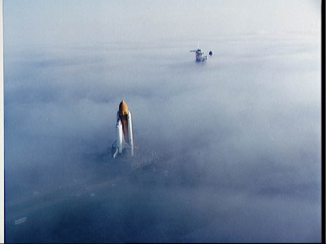 """Two views of the """"Challenger"""" being rolled out to pad 39A in the fog STS-6"""