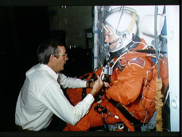 STS-41 MS Akers assisted by technician on SMS middeck at JSC