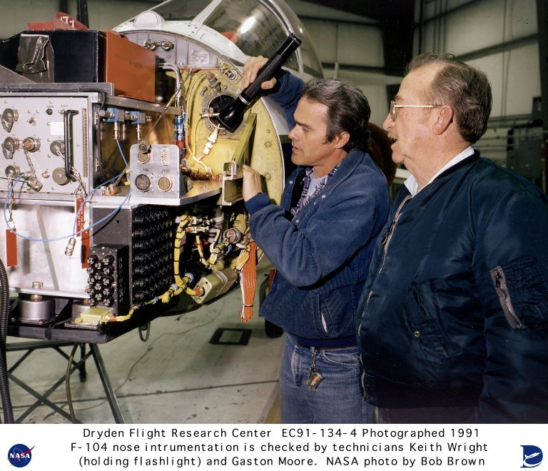 Avionics technician Keith E. Wright (holding the flashlight) is showing Inspector Gaston A. Moore the new installation of instrumentation on the nose shelf of an F-104 at the NASA Ames - Dryden Flight Research Facility. The nose section of an F-104 is composed of a shelf that is attached to the bulkhead of the airplane and holds instrumentation enclosed by a nose cone. The nose cone is similar to a drawer. When open it reveals the instrumentation for repairs and new installations, and when closed it is held in place by fasteners for flight.