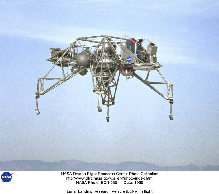"""In this 1965 NASA Flight Reserch Center photograph the Lunar Landing Research Vehicle (LLRV) number 1 is shown in flight. When Apollo planning was underway in 1960, NASA was looking for a simulator to profile the descent to the Moon's surface. Three concepts surfaced: an electronic simulator, a tethered device, and the ambitious Dryden contribution, a free-flying vehicle. All three became serious projects, but eventually the NASA Flight Research Center's (FRC) Landing Research Vehicle (LLRV) became the most significant one. Hubert M. Drake is credited with originating the idea, while Donald Bellman and Gene Matranga were senior engineers on the project, with Bellman, the project manager. Simultaneously, and independently, Bell Aerosystems Company, Buffalo, N.Y., a company with experience in vertical takeoff and landing (VTOL) aircraft, had conceived a similar free-flying simulator and proposed their concept to NASA headquarters. NASA Headquarters put FRC and Bell together to collaborate. The challenge was; to allow a pilot to make a vertical landing on Earth in a simulated Moon environment, one sixth of the Earth's gravity and with totally transparent aerodynamic forces in a """"free flight"""" vehicle with no tether forces acting on it. Built of tubular aluminum like a giant four-legged bedstead, the vehicle was to simulate a lunar landing profile from around 1500 feet to the Moon's surface. To do this, the LLRV had a General Electric CF-700-2V turbofan engine mounted vertically in gimbals, with 4200 pounds of thrust. The engine, using JP-4 fuel, got the vehicle up to the test altitude and was then throttled back to support five-sixths of the vehicle's weight, simulating the reduced gravity of the Moon. Two hydrogen-peroxide lift rockets with thrust that could be varied from 100 to 500 pounds handled the LLRV's rate of descent and horizontal translations. Sixteen smaller hydrogen-peroxide rockets, mounted in pairs, gave the pilot control in pitch, yaw, and roll. On the L"""