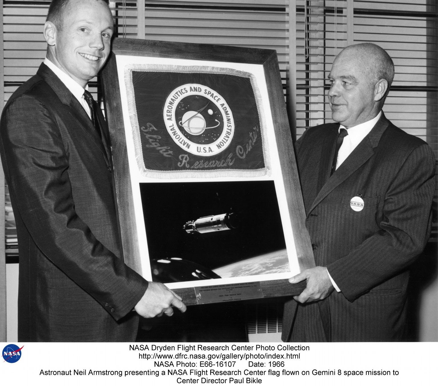 Astronaut Neil Armstrong presenting a NASA Flight Research Center flag flown on Gemini 8 space missi