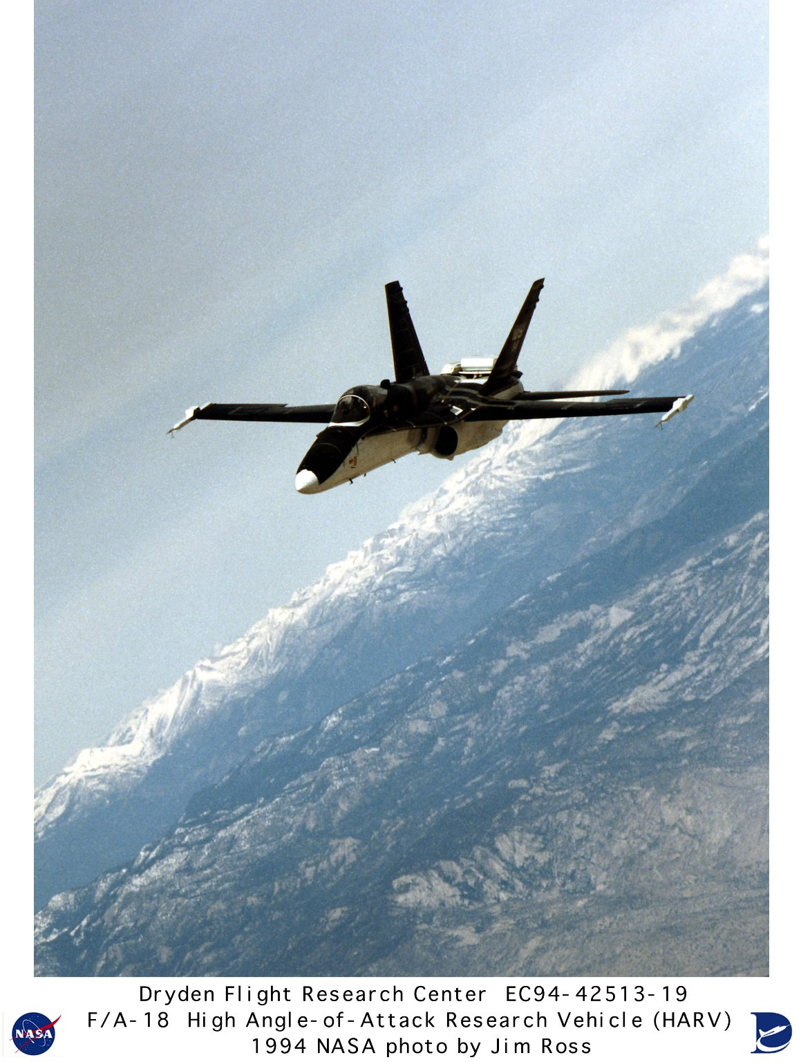 F-18 HARV in banked flight over snow-capped mountains