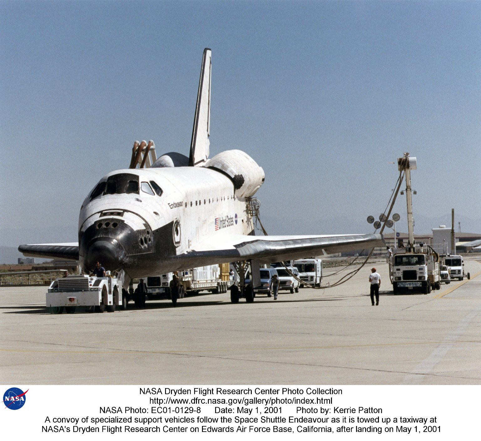 A convoy of specialized support vehicles follow the Space Shuttle Endeavour as it is towed up a taxi