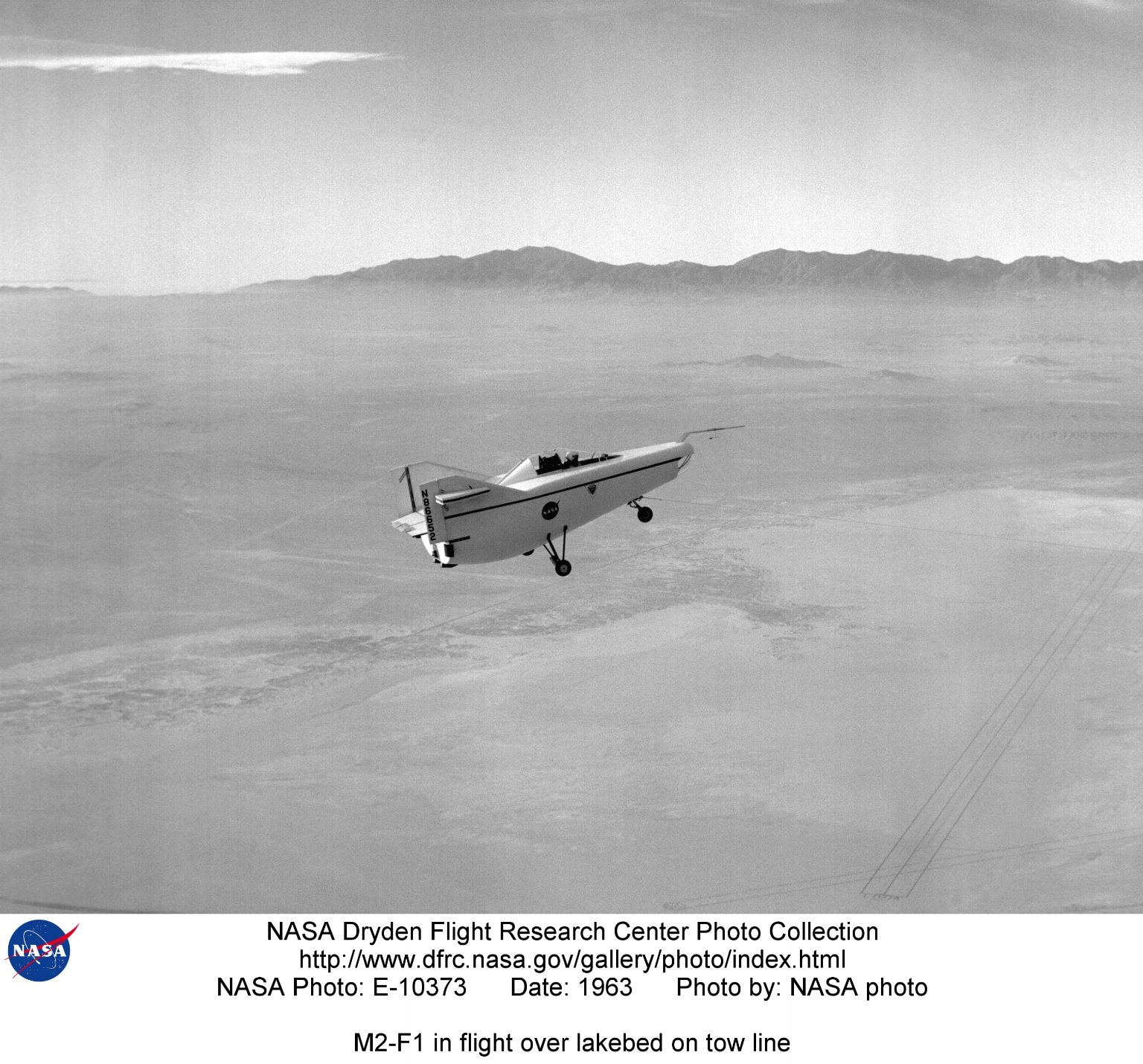 M2-F1 in flight over lakebed on tow line