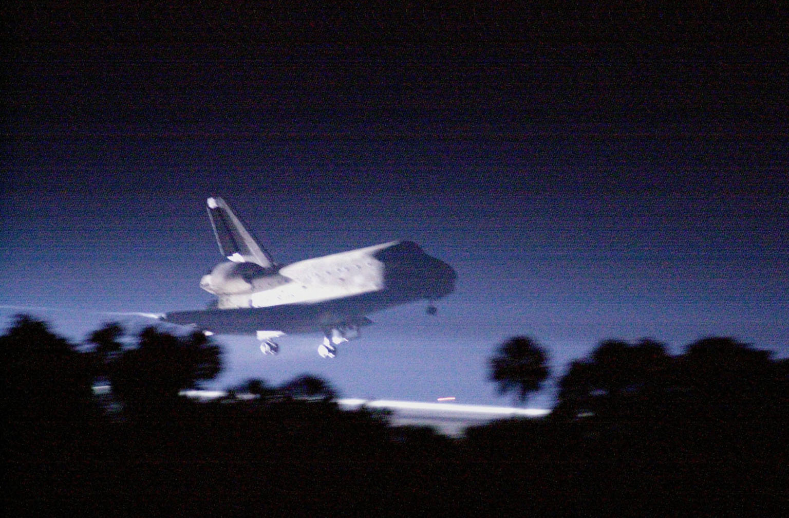 """KENNEDY SPACE CENTER, Fla. -- Landing lights illuminate the night sky as Space Shuttle Atlantis approaches touchdown on KSC's Shuttle Landing Facility Runway 15 to complete the 9-day, 20-hour, 9-minute-long STS-101 mission. At the controls are Commander James D. Halsell Jr. and Pilot Scott """"Doc"""" Horowitz. Also onboard the orbiter are Mission Specialists Mary Ellen Weber, James S. Voss, Jeffrey N. Williams, Susan J. Helms and Yury Usachev of Russia. The crew is returning from the third flight to the International Space Station. This was the 98th flight in the Space Shuttle program and the 21st for Atlantis, also marking the 51st landing at KSC, the 22nd consecutive landing at KSC, and the 29th in the last 30 Shuttle flights. Main gear touchdown was at 2:20:17 a.m. EDT, landing on orbit 155 of the mission. Nose gear touchdown was at 2:20:30 a.m. EDT, and wheel stop at 2:21:19 a.m. EDT"""