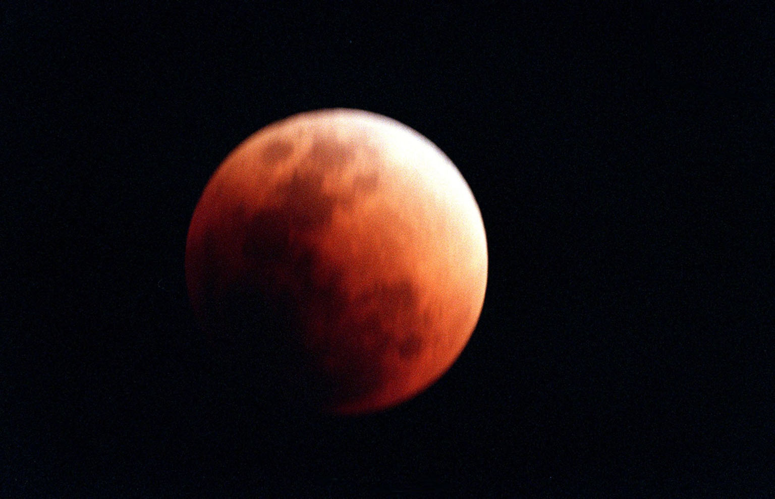In this lunar eclipse viewed from Merritt Island, Fla., at midnight, the full moon takes on a dark red color because it is being lighted slightly by sunlight passing through the Earth's atmosphere. This light has the blue component preferentially scattered out (this is also why the sky appears blue from the surface of the Earth), leaving faint reddish light to illuminate the Moon during the eclipse. Eclipses occur when the Sun, Earth and Moon line up. They are rare because the Moon usually passes above or below the imaginary line connecting Earth and the Sun. The Earth casts a shadow that the Moon can pass through -when it does, it is called a lunar eclipse