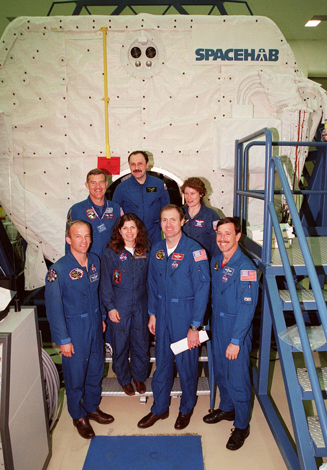 KENNEDY SPACE CENTER, FLA. -- The newly formed crew of STS-101 pose in front of the Spacehab double module in the Space Station Processing Facility. In the foreground from left are Mission Specialists Jeffrey Williams and Mary Ellen Weber, Commander James Halsell and Pilot Scott Horowitz; in the back are Mission Specialists James Voss, Yuri Usachev of Russia and Susan Helms. The crew will be responsible for preparing the International Space Station for the arrival of the Zvezda Service Module, expected to be launched by Russia in July 2000. Also, the crew will conduct one space walk to perform maintenance on the Space Station and deliver logistics and supplies. This will be the third assembly flight for the Space Station. STS-101 is scheduled to launch no earlier than April 13 from Launch Pad 39A