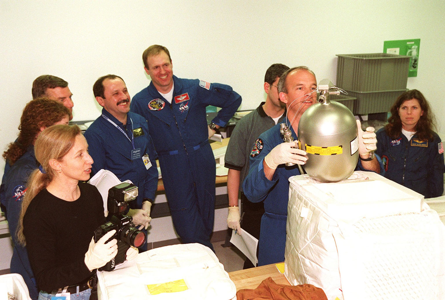 KENNEDY SPACE CENTER, FLA. -- Members of the STS-101 crew share a light moment during Crew Equipment Interface Test (CEIT) activities at SPACEHAB, in Cape Canaveral, Fla. Documenting the occasion is astronaut Marsha Ivins (far left, with camera). Standing behind her (left to right) are Mission Specialists Susan Helms, James Voss and Yuri Usachev; Commander James Halsell; and Mission Specialists Jeffrey Williams (holding tank) and Mary Ellen Weber. During a CEIT, a Shuttle crew becomes familiar with some of the equipment they will be working with on their mission. The STS-101 crew will be responsible for preparing the Space Station for the arrival of the Zvezda Service Module, expected to be launched by Russia in July 2000. Also, the crew will conduct one space walk to perform maintenance on the Space Station and deliver logistics and supplies. This will be the third assembly flight for the Space Station. STS-101 is scheduled to launch no earlier than April 13 from Launch Pad 39A