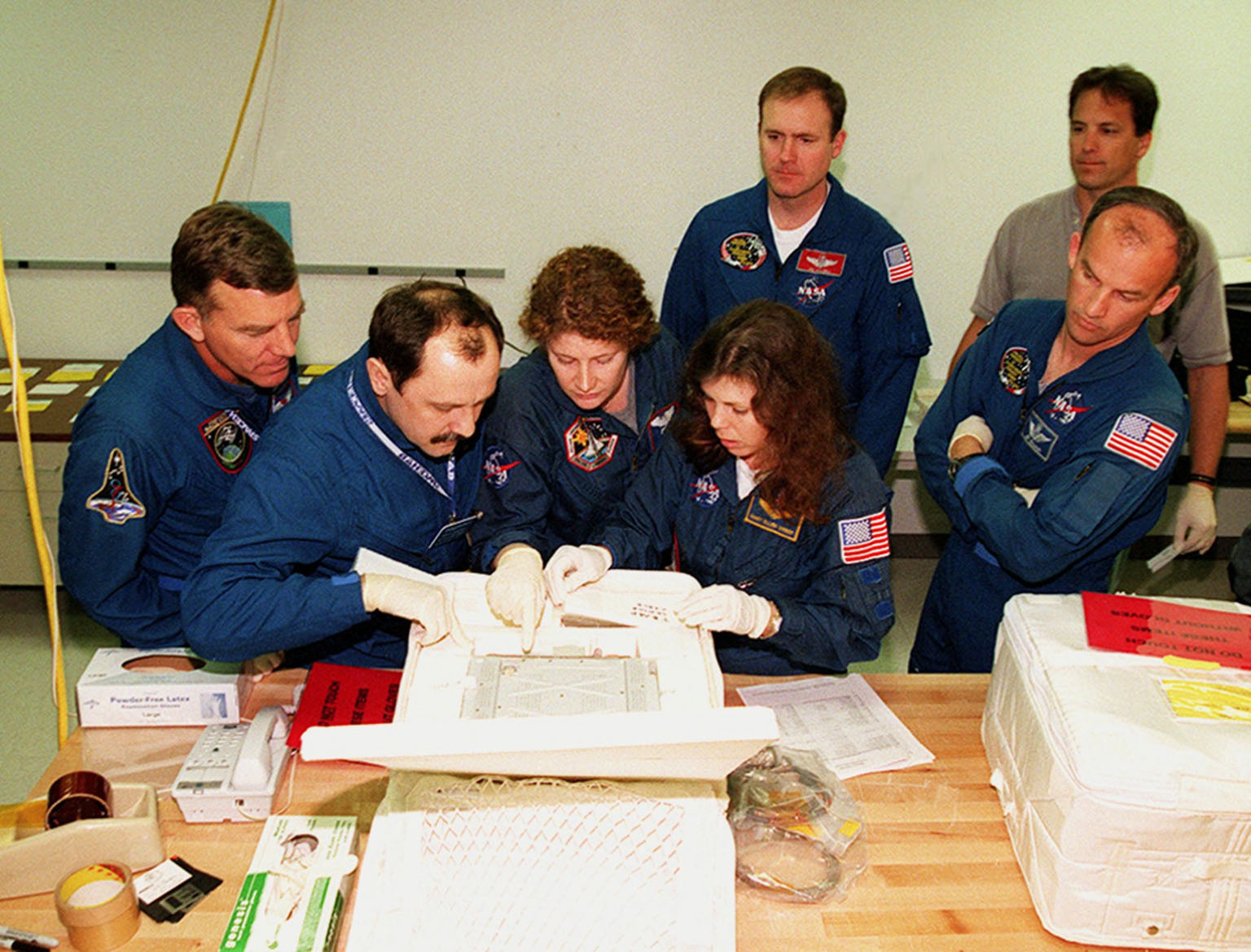 KENNEDY SPACE CENTER, FLA. -- At SPACEHAB, in Cape Canaveral, Fla., members of the STS-101 crew take part in Crew Equipment Interface Test (CEIT) activities, learning about some of the equipment they will be working with on their mission to the International Space Station. Looking over one of the elements are Mission Specialists James Voss, Yuri Usachev of Russia, Susan Helms and Mary Ellen Weber. Behind them is Commander James Halsell; at right is Mission Specialist Jeffrey Williams. The crew will be responsible for preparing the Space Station for the arrival of the Zvezda Service Module, expected to be launched by Russia in July 2000. Also, the crew will conduct one space walk to perform maintenance on the Space Station and deliver logistics and supplies. This will be the third assembly flight for the Space Station. STS-101 is scheduled to launch no earlier than April 13 from Launch Pad 39A