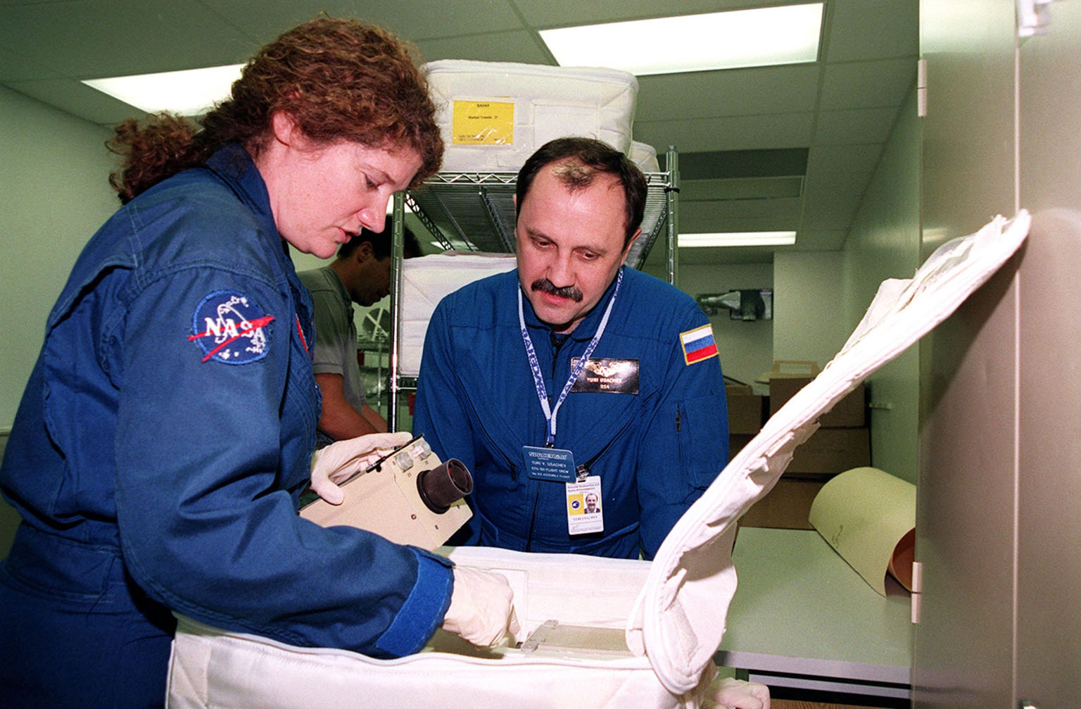 KENNEDY SPACE CENTER, FLA. -- As part of Crew Equipment Interface Test (CEIT) activities at SPACEHAB, in Cape Canaveral, Fla., STS-101 Mission Specialists Susan Helms and Yuri Usachev of Russia look over some of the equipment for their mission to the International Space Station. Other members of the crew taking part in the CEIT are Commander James Halsell, Pilot Scott Horowitz, and Mission Specialists Mary Ellen Weber, James Voss, and Jeffrey Williams. The STS-101 crew will be responsible for preparing the Space Station for the arrival of the Zvezda Service Module, expected to be launched by Russia in July 2000. Also, the crew will conduct one space walk to perform maintenance on the Space Station and deliver logistics and supplies. This will be the third assembly flight for the Space Station. STS-101 is scheduled to launch no earlier than April 13 from Launch Pad 39A