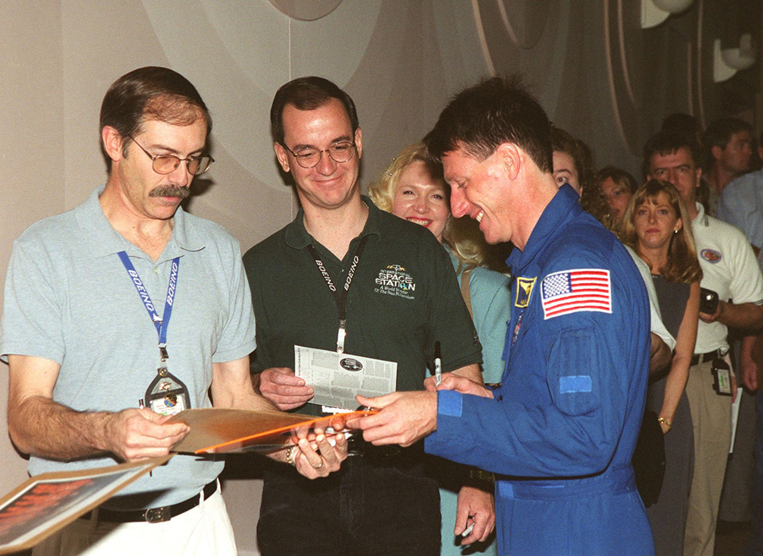 STS-103 Mission Specialist Michael Foale autographs mementos for Boeing-KSC employees. Foale and other crew members gave a presentation at the Center for employees and VIPs about their mission to service the Hubble Space Telescope. STS-103 launched Dec. 19, 1999, and landed Dec. 27, 1999, after a successful mission that included three space walks