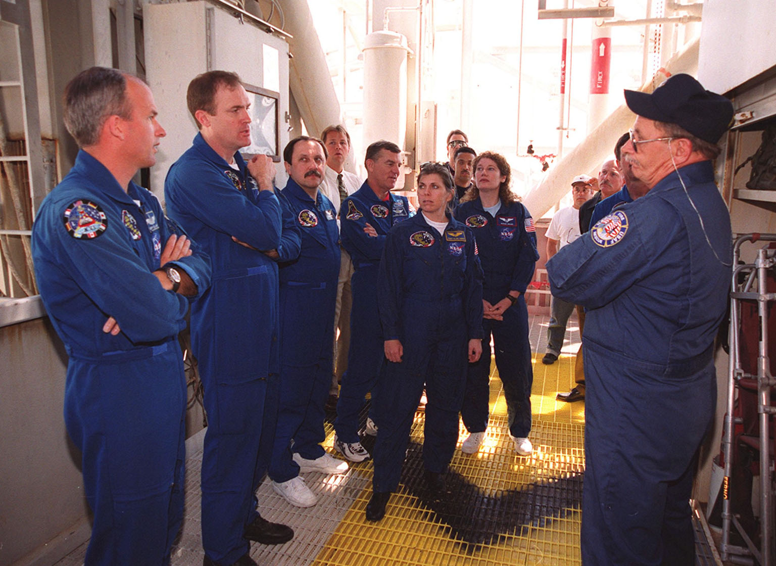 KENNEDY SPACE CENTER, Fla. -- At the 195-foot level of the Fixed Service Structure on Launch Pad 39A, the STS-101 crew take part in training during a Terminal Countdown Demonstration Test (TCDT). Activities during TCDT include emergency egress from the orbiter and a dress rehearsal for launch. Standing left to right are Pilot Scott Horowitz, Jeffrey Williams, Commander James Halsell, and Mission Specialists Yury Usachev, James Voss, Mary Ellen Weber, and Susan Helms. At right is trainer Capt. George Hoggard of the KSC/CCAS Fire Department. Not seen in the photo is Pilot Scott Horowitz. During their mission to the International Space Station, the STS-101 crew will be delivering logistics and supplies, plus preparing the Station for the arrival of the Zvezda Service Module, expected to be launched by Russia in July 2000. Also, the crew will conduct one space walk to perform maintenance on the Space Station. This will be the third assembly flight for the Space Station. STS-101 is scheduled to launch April 24 at 4:15 p.m. from Launch Pad 39A