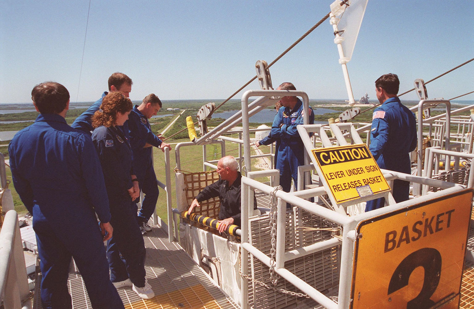 KENNEDY SPACE CENTER, Fla. -- At the 195-foot level of the Fixed Service Structure on Launch Pad 39A, the STS-101 crew get instruction in emergency egress in a slidewire basket during a Terminal Countdown Demonstration Test (TCDT). From left are Mission Specialist Yury Usachev and Susan Helms; Commander James Halsell; Mission Specialists James Voss, Mary Ellen Weber standing behind Jeffrey Williams; and Pilot Scott Horowitz. During their mission to the International Space Station, the STS-101 crew will be delivering logistics and supplies, plus preparing the Station for the arrival of the Zvezda Service Module, expected to be launched by Russia in July 2000. Also, the crew will conduct one space walk to perform maintenance on the Space Station. This will be the third assembly flight for the Space Station. STS-101 is scheduled to launch April 24 at 4:15 p.m. from Launch Pad 39A