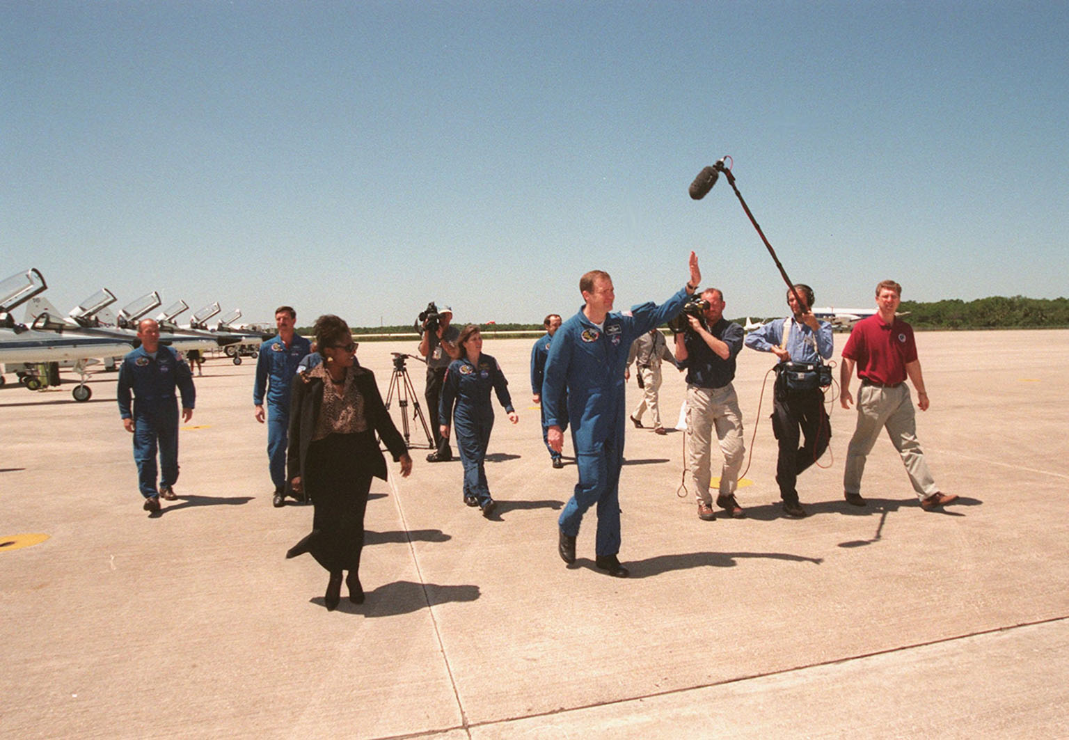 KENNEDY SPACE CENTER, FLA. -- At the Shuttle Landing Facility, STS-101 Commander James Halsell waves to the media as he and other crew members cross the tarmac to a waiting bus. At right is a film crew; in the foreground at left is Delores Green, flight crew support specialist lead for the astronaut crew quarters. Other crew members in the background are Mission Specialist Jeffrey Williams, Pilot Scott Horowitz, and Mission Specialists Mary Ellen Weber and Yury Usachev. Not visible in the photo is Mission Specialist Susan Helms. During their mission to the International Space Station, the STS-101 crew will be delivering logistics and supplies, plus preparing the Station for the arrival of the Zvezda Service Module, expected to be launched by Russia in July 2000. Also, the crew will conduct one space walk to perform maintenance on the Space Station. This will be the third assembly flight for the Space Station. STS-101 is scheduled to launch April 24 at 4:15 p.m. from Launch Pad 39A