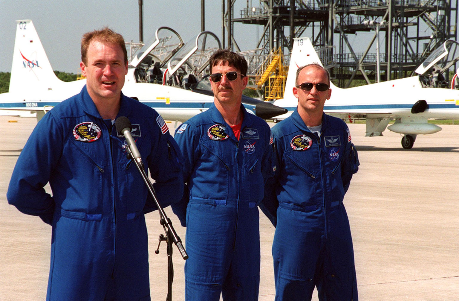 """After arriving at the Shuttle Landing Facility for their launch preparations, the STS-101 crew pauses to greet the media. At the microphone is Commander James Halsell. Next to him (left to right) are Pilot Scott """"Doc"""" Horowitz and Mission Specialist Jeffrey Williams. Other crew members not shown are Mission Specialists Mary Ellen Weber, James Voss, Susan Helms and Yury Usachev of Russia. The mission will take the crew to the International Space Station, delivering logistics and supplies, plus preparing the Station for the arrival of the Zvezda Service Module, expected to be launched by Russia in July 2000. Also, the crew will conduct one space walk to perform maintenance on the Space Station. This will be the third assembly flight for the Space Station. Launch is targeted for April 24 at about 4:15 p.m. EDT from Launch Pad 39A"""
