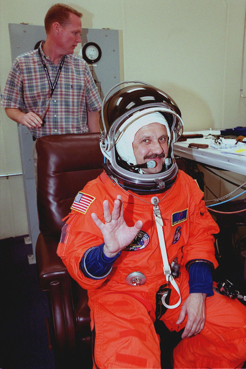 During pre-launch preparations in the Operations and Checkout Building, STS-101 Mission Specialist Yury Usachev of Russia waves while waiting for his launch and entry suit to be checked. Mission STS-101 will take the crew to the International Space Station to deliver logistics and supplies, plus prepare the Station for the arrival of the Zvezda Service Module, expected to be launched by Russia in July 2000. The crew will conduct one space walk to perform maintenance on the Space Station as well. This will be the third assembly flight for the Space Station. Launch is targeted for April 24 at about 4:15 p.m. EDT from Launch Pad 39A