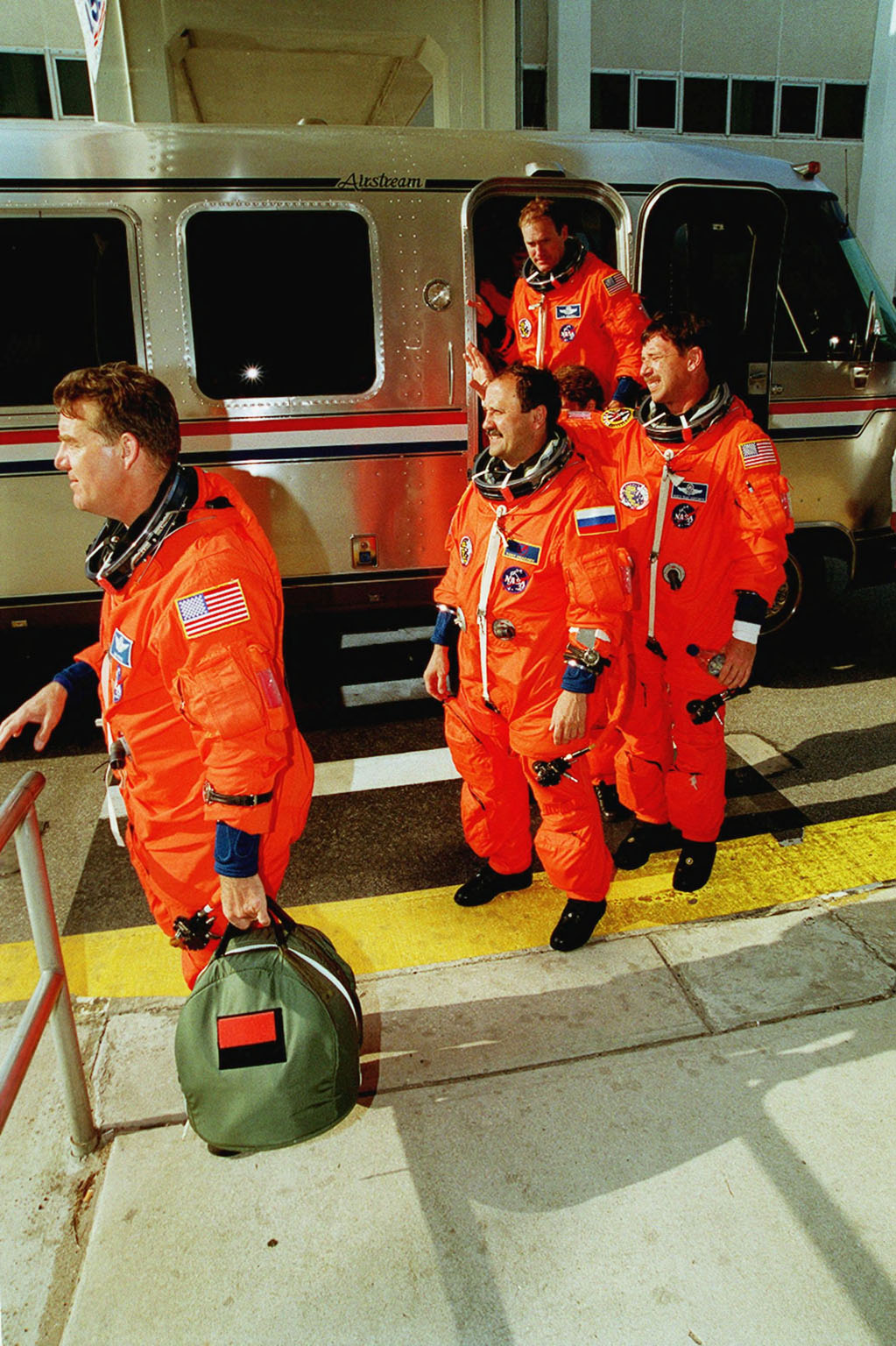 The STS-101 crew returns to the Operations and Checkout Building after the launch was scrubbed due to cross winds at the KSC Shuttle Landing Facility gusting above 20 knots. Flight rules require cross winds at the SLF to be no greater than 15 knots in case of a contingency Shuttle landing. Shown leaving the Astrovan are (left to right) Mission Specialists James S. Voss and Yury Usachev of Russia; Pilot Scott J. Horowitz; and Commander James D. Halsell Jr. in the doorway. Weather conditions will be reevaluated for another launch try on April 25. The mission will take the crew to the International Space Station to deliver logistics and supplies and to prepare the Station for the arrival of the Zvezda Service Module, expected to be launched by Russia in July 2000. Also, the crew will conduct one space walk. This will be the third assembly flight to the Space Station. The mission is expected to last about 10 days