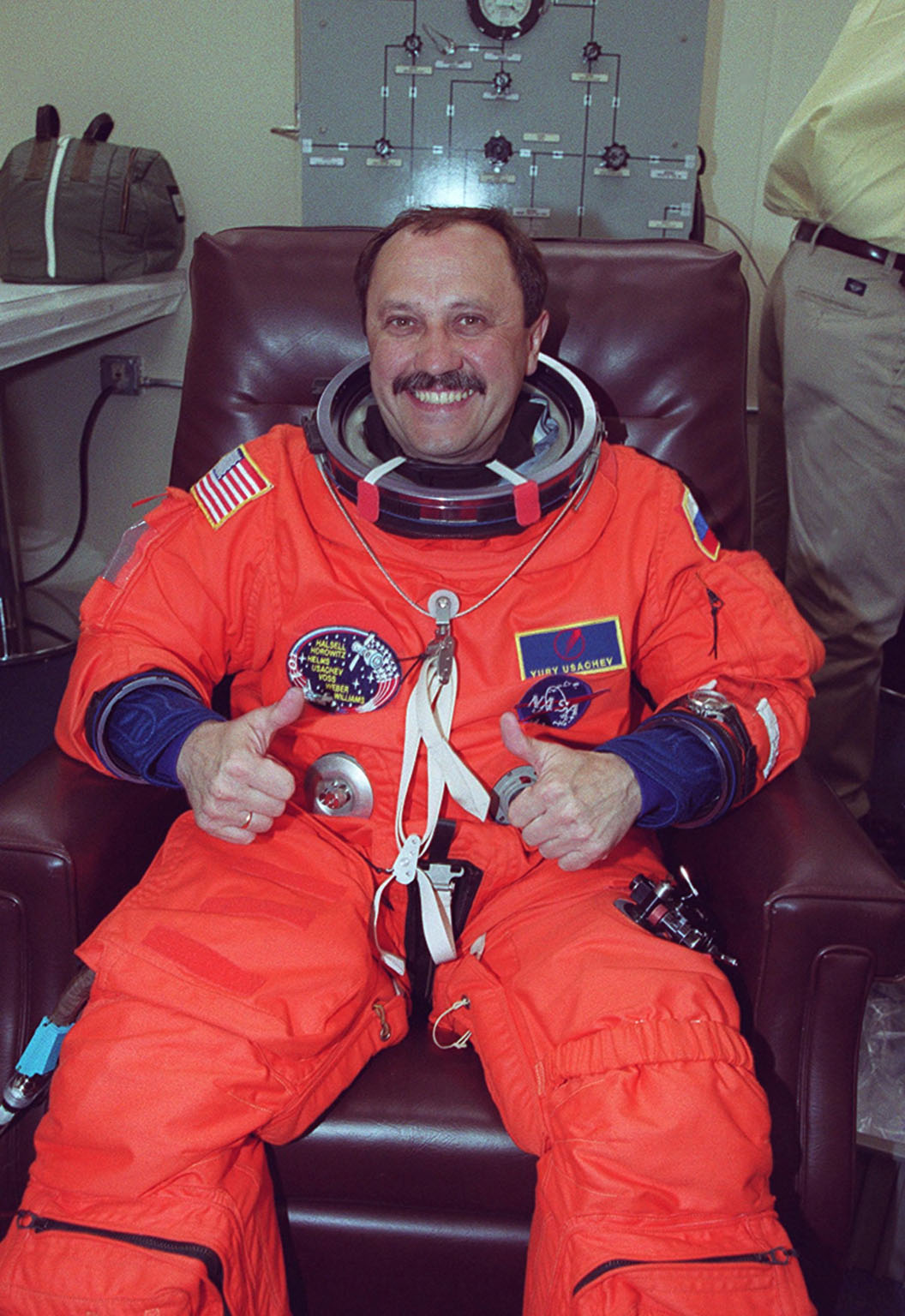 In the Operations and Checkout Building, STS-101 Mission Specialist Yury Usachev of Russia gives two thumbs up while waiting for final check of his launch and entry suit before heading a third time to Launch Pad 39A and launch of Space Shuttle Atlantis. The previous two launch attempts were scrubbed due to high cross winds at the Shuttle Landing Facility. The mission will take the crew to the International Space Station to deliver logistics and supplies and to prepare the Station for the arrival of the Zvezda Service Module, expected to be launched by Russia in July 2000. Also, the crew will conduct one space walk. This is the third assembly flight to the Space Station. After the 10-day mission, Atlantis is expected to land at KSC May 6 at about 12:03 p.m. EDT