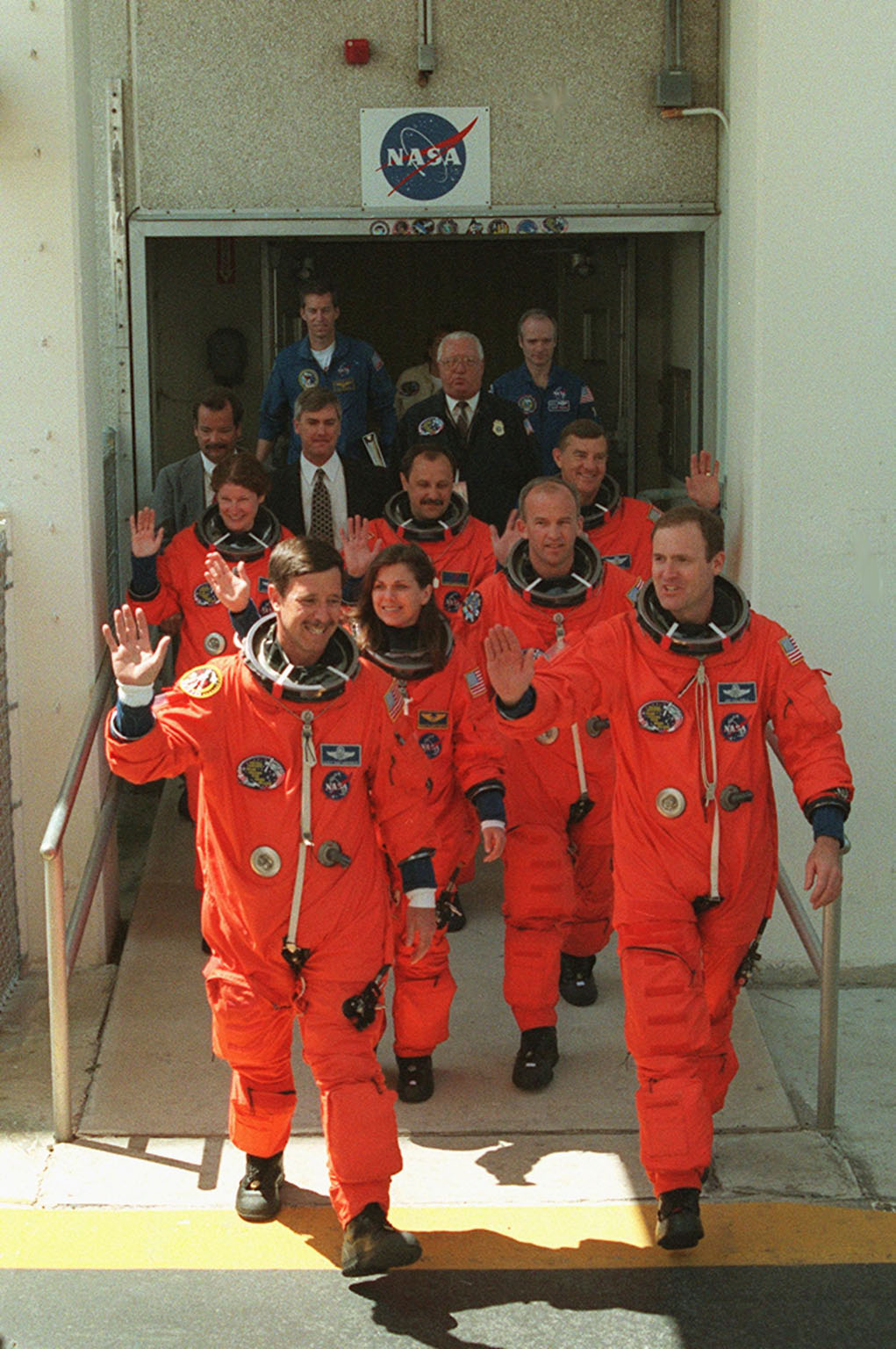 The STS-101 crew wave to onlookers as they leave the Operations and Checkout Building enroute a third time to Launch Pad 39A for launch of Space Shuttle Atlantis. The previous two launch attempts were scrubbed due to high cross winds at the Shuttle Landing Facility. They are (front) Pilot Scott J. Horowitz (left) and Commander James D. Halsell Jr.; (middle) Mission Specialists Mary Ellen Weber and Jeffrey N. Williams; (back) Mission Specialists Susan J. Helms, Yury Usachev of Russia and James S. Voss. The mission will take the crew to the International Space Station to deliver logistics and supplies and to prepare the Station for the arrival of the Zvezda Service Module, expected to be launched by Russia in July 2000. Also, the crew will conduct one space walk. This is the third assembly flight to the Space Station. After the 10-day mission, Atlantis is expected to land at KSC May 6 at about 12:03 p.m. EDT