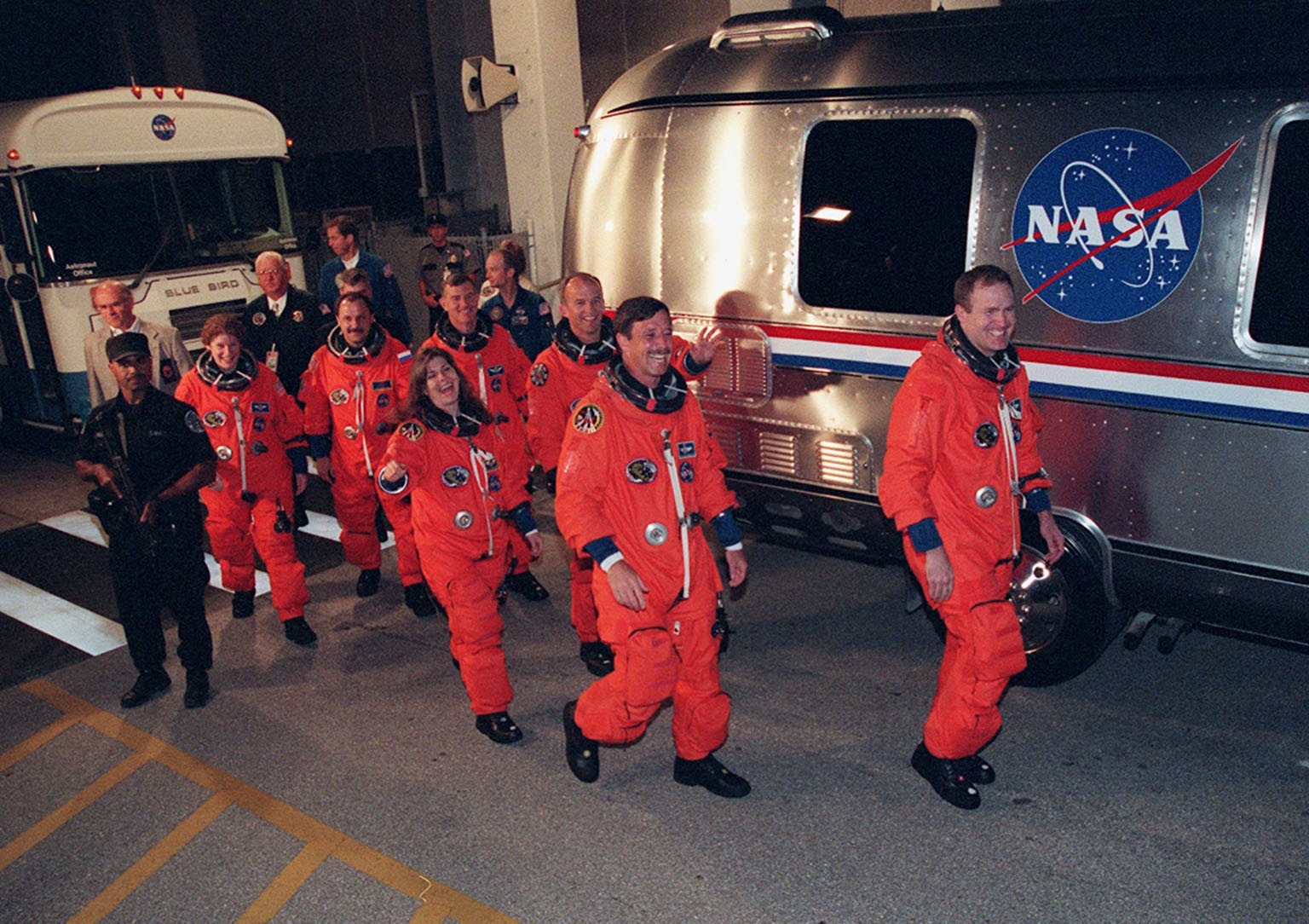The STS-101 crew wave and smile at onlookers as they head to the Astrovan for the trip to Launch Pad 39A and the fourth attempt at launch of Space Shuttle Atlantis. In their orange launch and entry suits, they are (left to right) Mission Specialists Susan J. Helms, Yury Usachev of Russia, James S. Voss, Mary Ellen Weber, Jeffrey N. Williams; Pilot Scott ?Doc? Horowitz; and Commander James D. Halsell Jr. The mission will take the crew to the International Space Station to deliver logistics and supplies and to prepare the Station for the arrival of the Zvezda Service Module, expected to be launched by Russia in July 2000. Also, the crew will conduct one space walk and will reboost the space station from 230 statute miles to 250 statute miles. This will be the third assembly flight to the Space Station. Liftoff of Space Shuttle Atlantis for the 10-day mission is scheduled for about 6:11 a.m. EDT from Launch Pad 39A. Landing is targeted for May 29 at 2:19 a.m. EDT