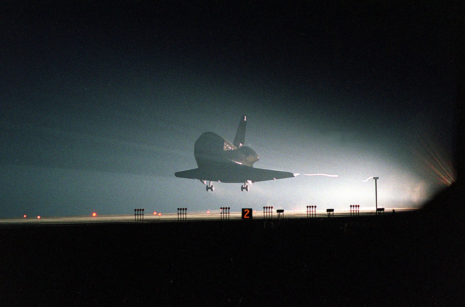 KENNEDY SPACE CENTER, Fla. -- At KSC?s Shuttle Landing Facility, the lights on Runway 15 reveal Space Shuttle Atlantis as it nears touchdown, completing the 9-day, 20-hour, 9-minute-long STS-101 mission. At the controls are Commander James D. Halsell Jr. and Pilot Scott ?Doc? Horowitz. Also onboard the orbiter are Mission Specialists Mary Ellen Weber, James S. Voss, Jeffrey N. Williams, Susan J. Helms and Yury Usachev of Russia. The crew is returning from the third flight to the International Space Station. This was the 98th flight in the Space Shuttle program and the 21st for Atlantis, also marking the 51st landing at KSC, the 22nd consecutive landing at KSC, the 14th nighttime landing in Shuttle history and the 29th in the last 30 Shuttle flights. Main gear touchdown was at 2:20:17 a.m. EDT May 29 , landing on orbit 155 of the mission. Nose gear touchdown was at 2:20:30 a.m. EDT, and wheel stop at 2:21:19 a.m. EDT