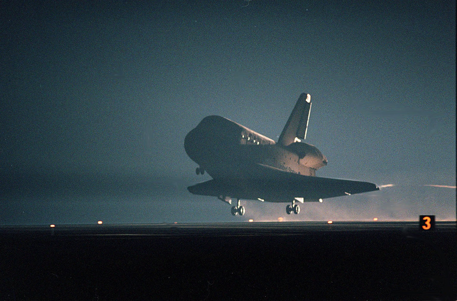 KENNEDY SPACE CENTER, Fla. -- Seen in the landing lights, an illuminated Space Shuttle Atlantis approaches touchdown on KSC?s Shuttle Landing Facility Runway 15 to complete the 9-day, 20-hour, 9-minute-long STS-101 mission. At the controls are Commander James D. Halsell Jr. and Pilot Scott ?Doc? Horowitz. Also onboard the orbiter are Mission Specialists Mary Ellen Weber, James S. Voss, Jeffrey N. Williams, Susan J. Helms and Yury Usachev of Russia. The crew is returning from the third flight to the International Space Station. This was the 98th flight in the Space Shuttle program and the 21st for Atlantis, also marking the 51st landing at KSC, the 22nd consecutive landing at KSC, the 14th nighttime landing in Shuttle history and the 29th in the last 30 Shuttle flights. Main gear touchdown was at 2:20:17 a.m. EDT May 29 , landing on orbit 155 of the mission. Nose gear touchdown was at 2:20:30 a.m. EDT, and wheel stop at 2:21:19 a.m. EDT